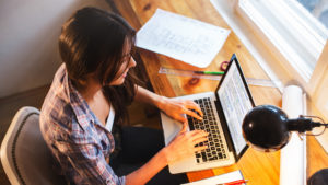 Young female blogger working at home.She sitting in her working room and typing something on laptop.